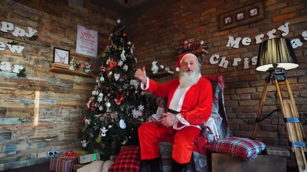 Joyful Santa Claus shows delight from room decorated with holidays and raises thumb up, sitting on big armchair