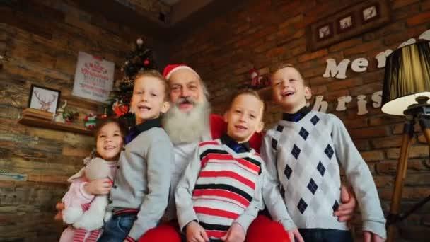 Radost chlapci a dívka hlasitě zpívaly vánoční písně s Santa Claus v místnosti zařízené dekorace strom