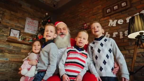 Gelukkige jongens en meisje zingen luid kerstliedjes met kerstman in