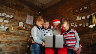 Kind guys help Santa Claus write letter in laptop in decorated room