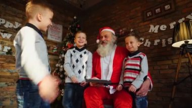 Little brothers boys teach Santa Claus to play on tablet in festively decorated room with decorated Christmas tree