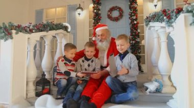 Happy mens children happy with New Years gift from Santa on porch of house with Christmas decorations and green Christmas tree