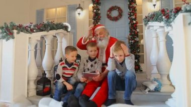 Santa and three brothers going through loss in game on tablet, sitting on stairs on porch of house decorated for holidays