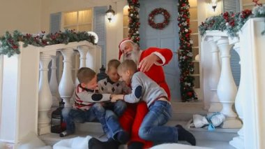 Christmas grandfather and little boys fool around on stairs on porch of decorated house