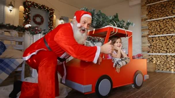 Dobří přátelé Santa a dívka pózuje na kameru na verandě domu velké zdobené na Vánoce