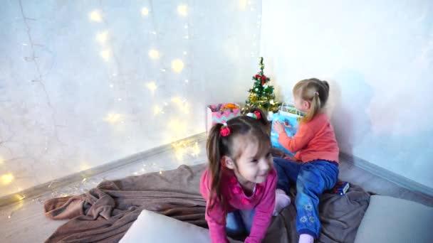 kisgyermekek, a lány nevetni és hülyéskedik, ült a padlón, és a szőnyeg, fal, girland és karácsonyfa délután háttere.