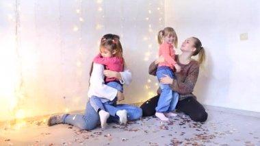 Két gyönyörű amerikai anya ül a padlóra és átölelve, kis lánya