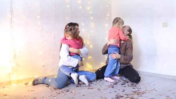 Dvě krásné americké maminky sedí na podlaze a objímání s malou dcery.