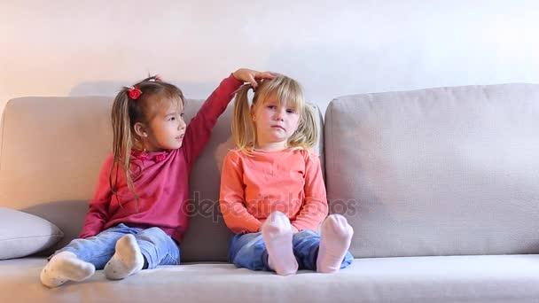 Malá holčička seděla na gauči a pláč, přítel uklidňuje a obejme dítě.
