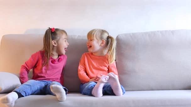 Két kislány játszani, és szórakozni a kanapéra a nappaliban