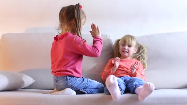 Two beautiful little girls play and fun to spend time on couch.