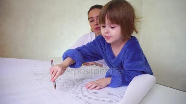 Mladá matka pomáhá dcera s výkresem, koncentrovaná dívky sedí v dobře osvětlené místnosti diskuse o okupaci