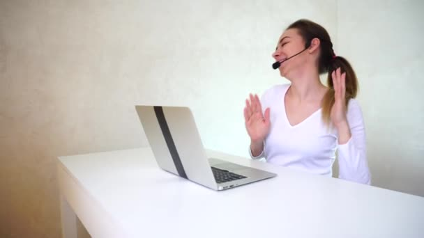 Young fair-haired woman with ponytail sitting near table with silver laptop in well-lit room and answering calls.
