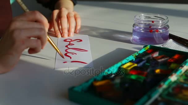 Writing phrase with brush and aquarelle.