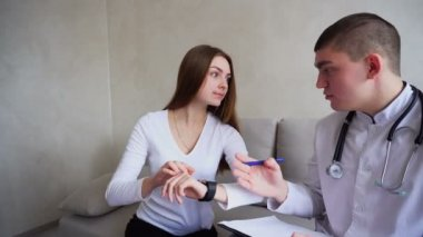 Doctor nephrologist and female patient study medical functions of smart Watch, use new technologies in office hospital.
