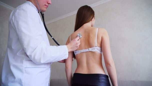 Erfahrener männlicher Therapeut diagnostiziert junge Frau, die nachmittags in heller Arztpraxis stand.