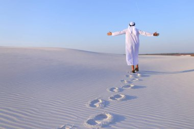 Joyful male Muslim walks through white sand desert and enjoys li