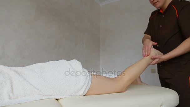 mužské masáž terapeut provádí stehno postup pacienta, který leží na gauči ve světlé kanceláři