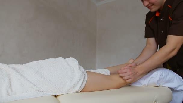 masáž terapeut provádí postup nohy pacienta, který leží na gauči ve světlé kanceláři
