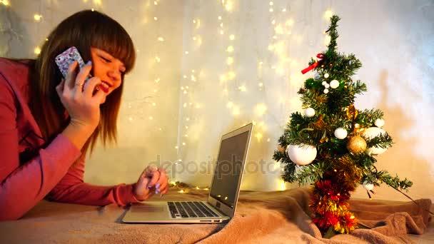 Veselá ženská osoba mluví o telefonu a zadáte zprávu na laptop