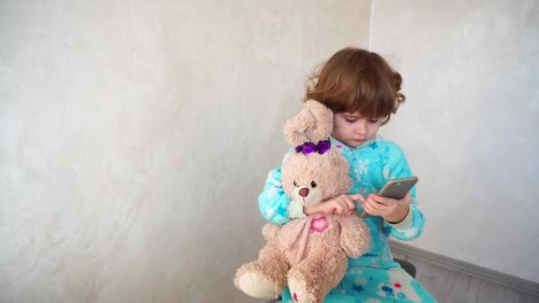 Little girl with friend listening music on phone.