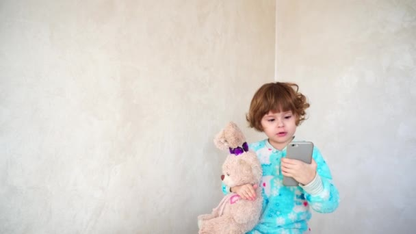 Small British kid dances with phone in hands.