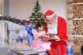 Malá holčička zpívat s Santa Claus.