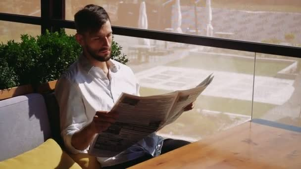 Handsome male person reading newspaper and wondering.