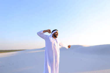 Happy Muslim guy walks through expanses of desert and rests with