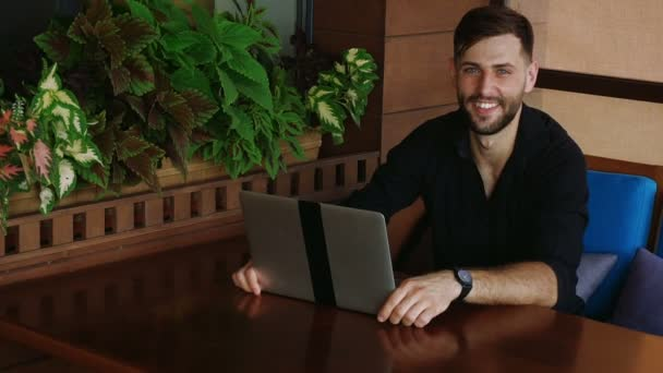 Happy businessman looking at camera working with laptop and talking in slow motion.