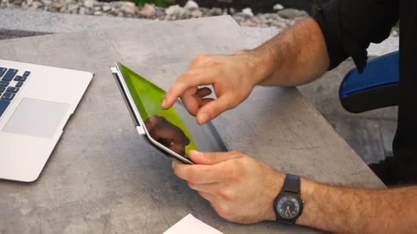 Detailní záběr rukou na tabletu s notebookem v pozadí