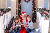 Šťastné děti hrají s Santa Claus.