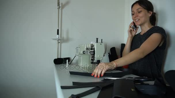 Slow motion seamstress discussing work with boss using smartphone