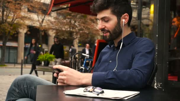 American boy listening to music at cafe with earphones and smartphone in slow motion.