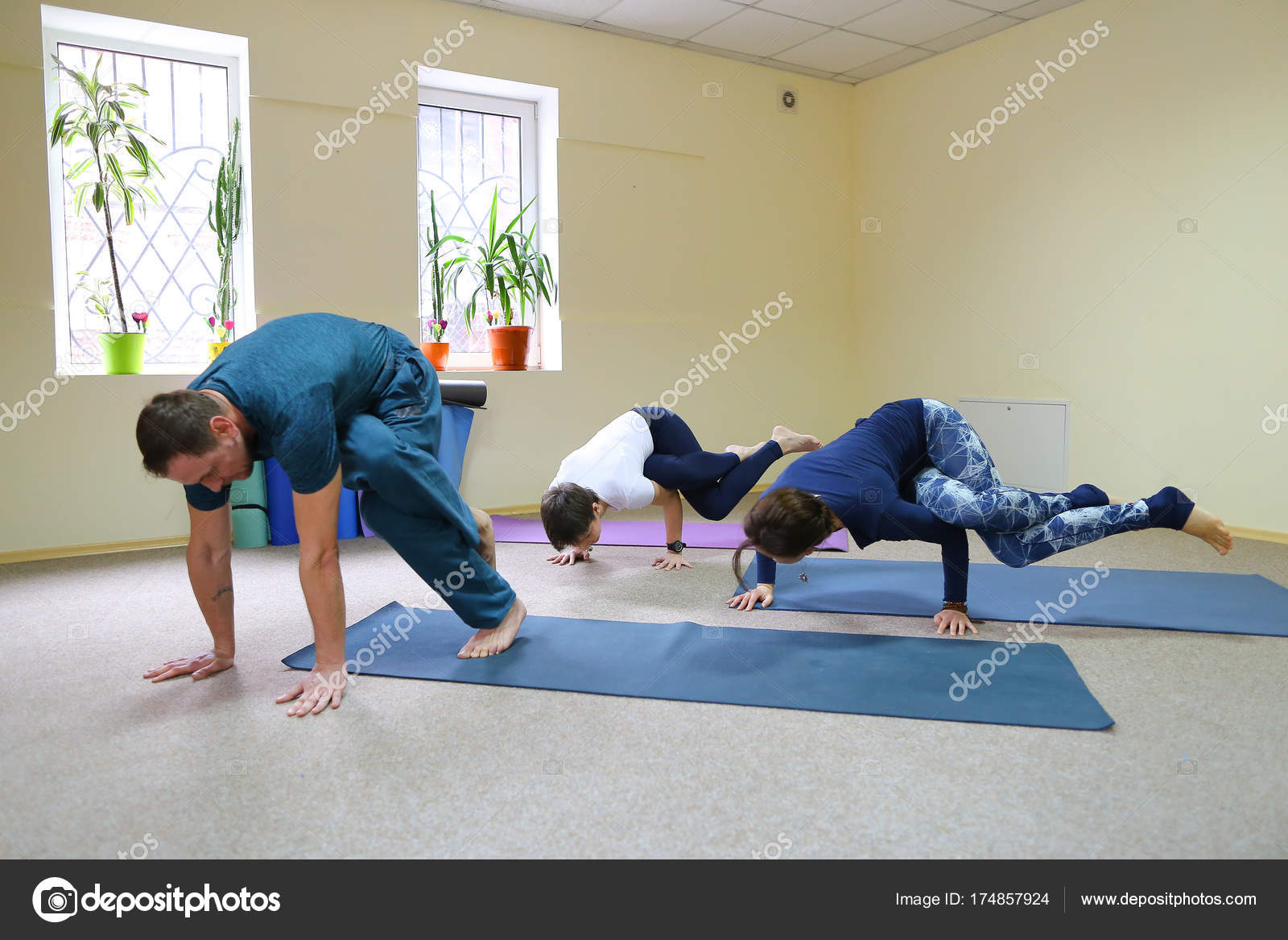 Three Young People Doing Yoga At Fitness Studio Stock Photo