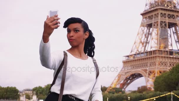 Pretty female standing on street not far from Eiffel Tower and making pictures