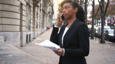 Concentrated girl talking on mobile, young business woman negotiated deal with big company.