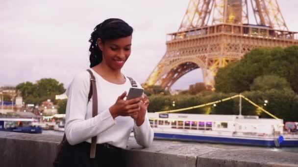 Mladá žena stojí na nábřeží v Paříži a sledování fotografií na smartphone