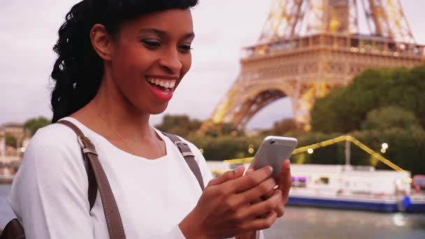 Smiling business woman standing on bridge and using smartphone