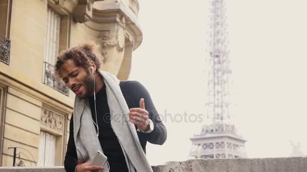 Mix krev hudba milenec těší nové sluchátka a smartphone blízko: Eiffel tower.