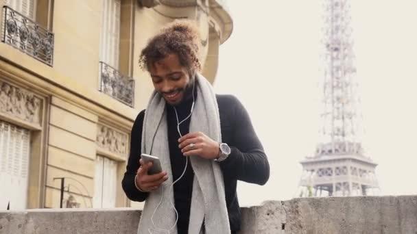 Polovina Afriky tourist poslechu nové písně v sluchátka s smartphone blízko: Eiffel tower
