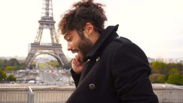 Mulatto businessman talking with partner on smartphone near Eifel Tower in slow motion.