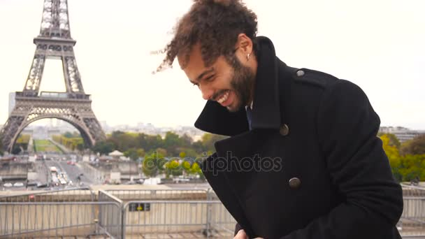 Mulatto laughing guy around Eiffel Tower with smartphone in slow motion.