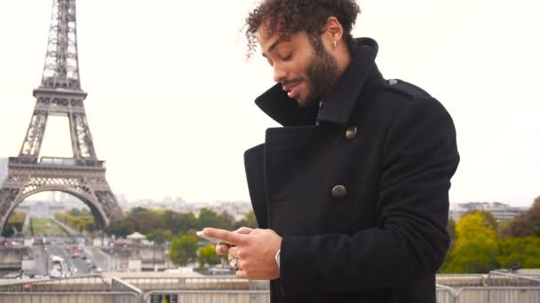 Zahraniční přítel chatování s francouzskou dívku na smartphone kolem Eiffelovy věže ve zpomaleném záběru