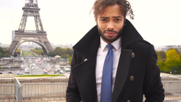 Mulat mužský model s úsměvem poblíž Eifellova věž v pomalém pohybu