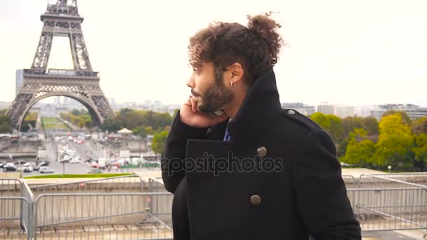 Zahraniční student v Paříži volání s smartphone blízko: Eiffel Tower v pomalém pohybu