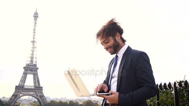 Cestovní správce pomocí notebooku s Eiffelova věž v pozadí v pomalém pohybu