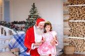 Veselý Santa Claus mluví s malou holčičku.