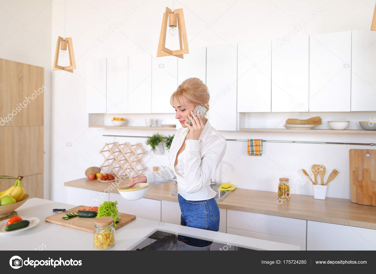 Cute female housewife chats on cellular and smiles, prepares sal ...