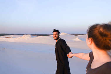Young male Muslim leads girl by hand and walks along desert at s